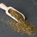 Cumin seeds in a wooden scoop.